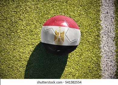 football ball with the national flag of egypt lies on the green field near the white line