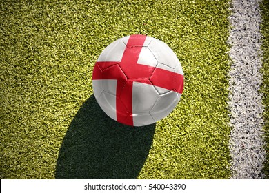 football ball with the national flag of england lies on the green field near the white line