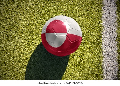 football ball with the national flag of greenland lies on the green field near the white line