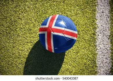 football ball with the national flag of iceland lies on the green field near the white line