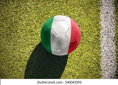 football ball with the national flag of italy lies on the green field near the white line