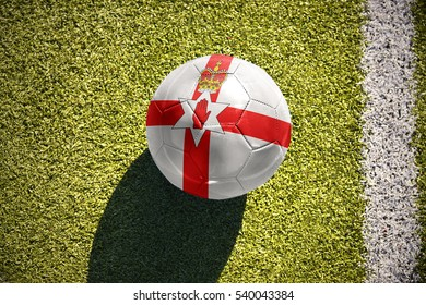 football ball with the national flag of northern ireland lies on the green field near the white line
