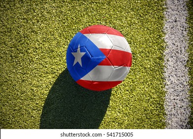 football ball with the national flag of puerto rico lies on the green field near the white line