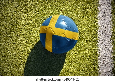 football ball with the national flag of sweden lies on the green field near the white line
