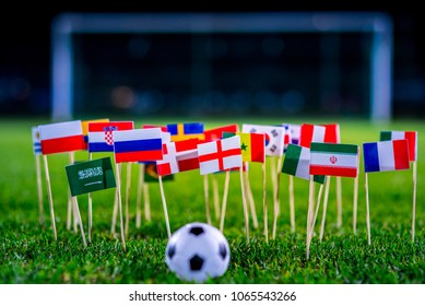 Football ball on green grass and all national flags