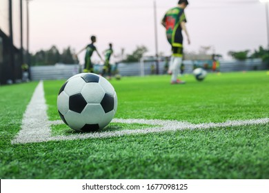 The football ball is placed in the corner of a small football field. And on the back there is a child rehearsing the ball on the training field Used as an illustration