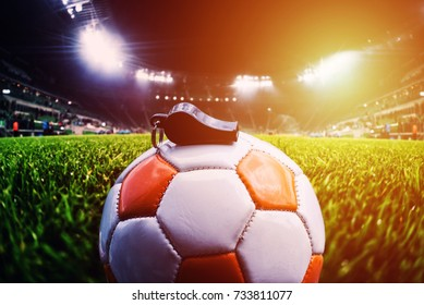 Football ball with whistle on the grass on soccer stadium, sunlight effect