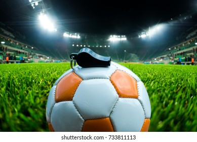 Football ball with whistle on the grass on soccer stadium