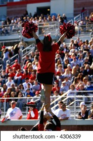 A football cheerleader is raised into the air in front of a large collegiate crowd.