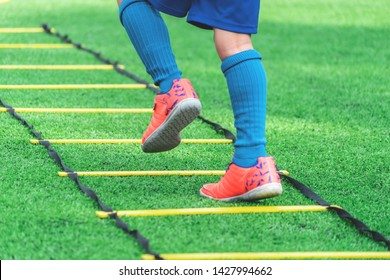 Football Child feet with orange soccer boots is running and training on agility speed ladder in soccer agility training drill in football Academy Development school.