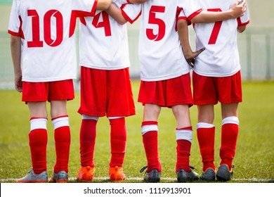 Football children team. Kids soccer substitute players standing together on a row. Football sports tournament for young boys. Four kids watching football penalties game on a pitch