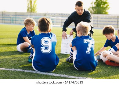 Football coach coaching kids. Soccer football training session for young boys. Young coach teaching children on football field. Football tactic education. Coach explains the strategy of the game