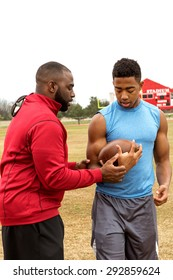 Football coach coaching a football player on the football field.