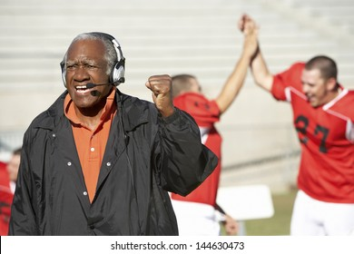 Football coach shouting and pumping fist with football players in the background