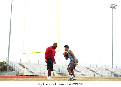Football coach training and teaching a football player.