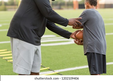 Football coach training a young student athlete.