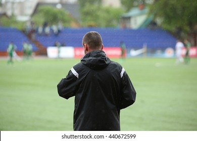 Football coach watching the match at rainy time