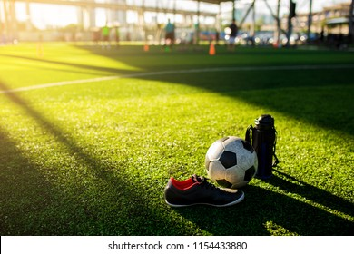 Football, cool flask and black red sports shoes on green artificial turf with blurry kid soccer player training. Sunshine and shadows of soccer training equipment.