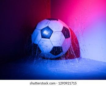 Football in the corner under spider net