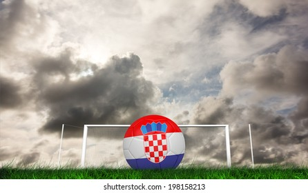Football in croatia colours against green grass under grey sky