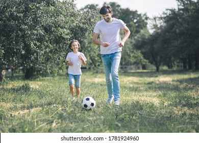 Football. Dark-haired boy and his father playing with the ball