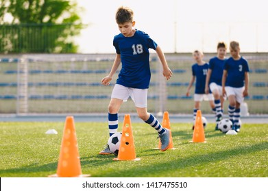 Football Drills: The Slalom Drill. Youth soccer practice drills. Young football players training on pitch. Soccer slalom cone drill. Boy in blue soccer jersey shirt running with ball between cones