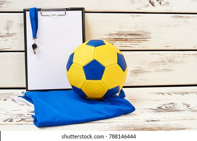 Football equipment and trainer's clipboard. Soccer ball and t-shirt in team colors. Season results and statistics.