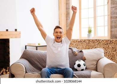 Football fan. Good-looking delighted well-built adolescent smiling and holding his arms up while sitting on the couch and a soccer ball near him