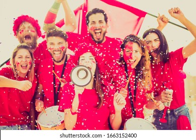 Football fan screaming, with red shirts in the stadium throwing confetti. Group of young people very excited about football. Sport and fun concept. focus on megaphone - Image