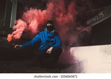 A football fan with a smoke bomb in his hands. Ultras fan with pyrotechnics in hand. A football fan in the smoke from a smoke bomb.