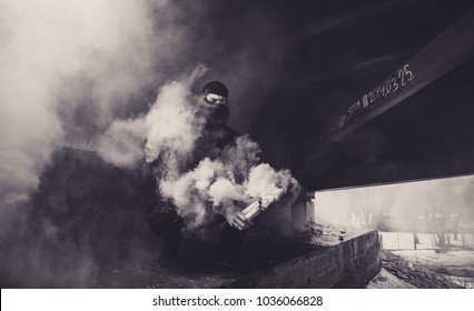 A football fan with a smoke bomb in his hands. Ultras fan with pyrotechnics in hand.. A football fan in the smoke from a smoke bomb.