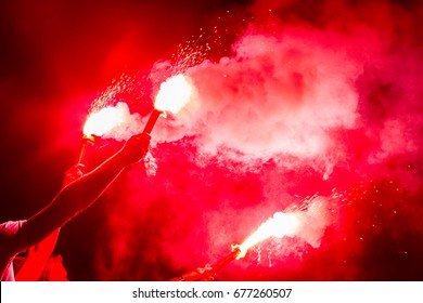 football fans are holding torches in fire during a match