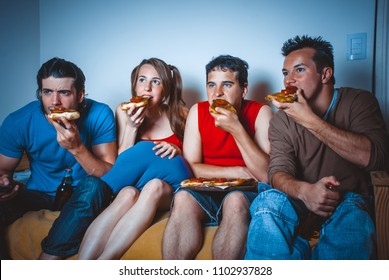 football fans on the couch near the TV with pizza and beer during the broadcast of the match
