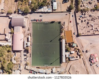 Football field located in a very poor and dry city looked from the air