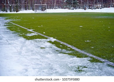 Football field in snow in the winter. A white marking on a green field and white gate for game in football.