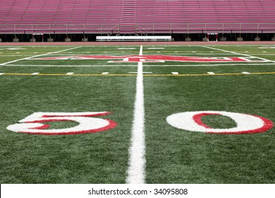 Football field view on 50 yard line with spectator stands