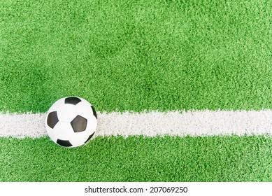 Football flag. Ball on white line on grass field.