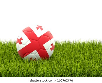 Football with flag of georgia on green grass