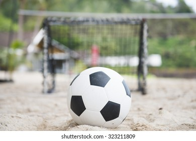 football in front of the mini goal on the sand, sport