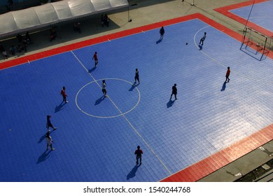 Football (Futsal) sports in the sun. The young players who played in the stadium became silhouettes. High angle view of Futsal competition.