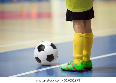 Football futsal training for children. Indoor soccer young player with a soccer ball in a sports hall. Player in yellow uniform. Sport background.