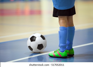 Football futsal training for children. Indoor soccer young player with a soccer ball in a sports hall. Player in blue uniform. Sport background.