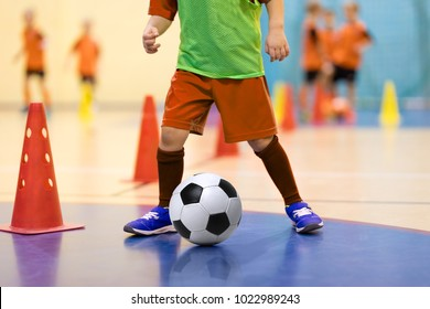 Football futsal training for children. Soccer training dribbling cone drill. Indoor soccer young player with a soccer ball in a sports hall. Player in orange uniform. Sport background.