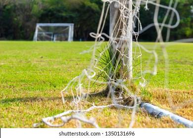 Football goal and goalpost with fresh green grass at stadium.