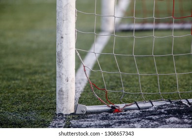 Football goal and goalpost near goal line on artificial soccer pitch abstract texture in winter