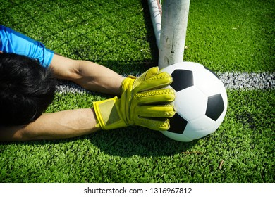 Football in goal with hand