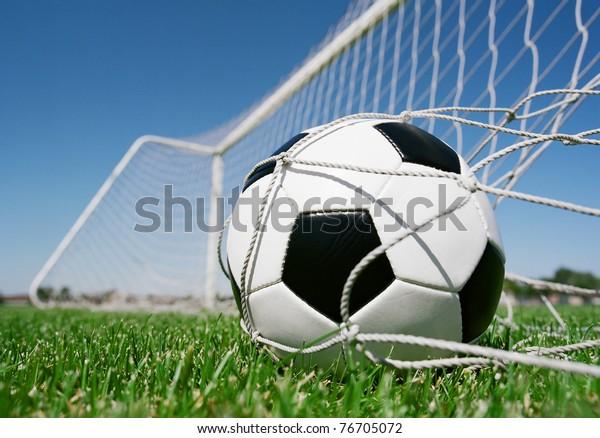Football in the goal net against blue sky