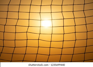 Football goal net at sunset. Meshed pattern with sun and sunset sky in background.