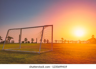 Football goal with net at sunset in tropical climate. Green field, palms and sunset sky with sun.