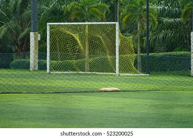 Football goal with  white post and yellow net at football field with green grass.
